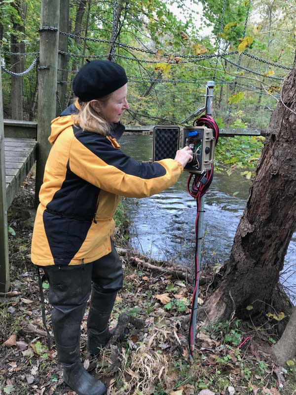 Carol Armstrong maintaining a stream sensor station.