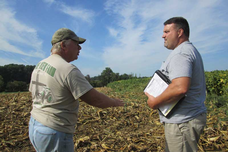 Farmers Jeremy Weaver and Jeff Frey talking at a no-till farm field.