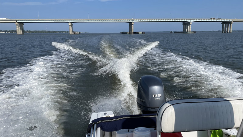 A motor boat on the Choptank River, with its wake and a bridge in the distance.