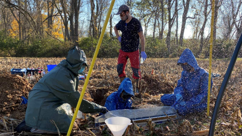 Four scientists collect simulated rainfall from soil in a cornfield in White Clay Creek watershed.